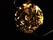 Metalliska inneslutningar i färglös syntetisk diamant tillverkad med HPHT teknik. Mörkfältsbelysning, förstoring 40x. Dessa inneslutningar är typiska för äldre syntetiska diamnter men ses sällan i modernare varianter. Denna bild är precis som alla andra bilder på www.gemmologi.se tagna av Jan Asplund.