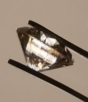 Syntetisk diamant tillverkd med CVD metod sedd mellan polariserande filter. Mönstret hos iridescensfärgerna ger ledtrådar till stenens syntetiska ursprung för den som har tillräklig kunskap.
