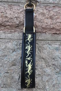 Svart skinn - Drakar  i guld på svart botten. Totalbredd 3,5 cm.