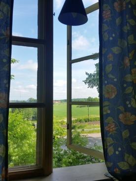 Kan du tänka dig den här utsikten rekommenderar jag att du bokar det norra rummet vårt i B&B. Om du sitter i karmstolen vid det lilla bordet framför fönstret har du koll på hur grödorna växer.