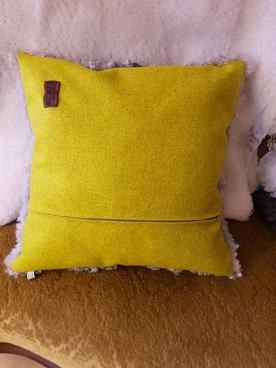 Nytillverkad kudde med lammskinn p ena sidan och snyggt ylletyg på andra sidan. En dragkedja som dekor.