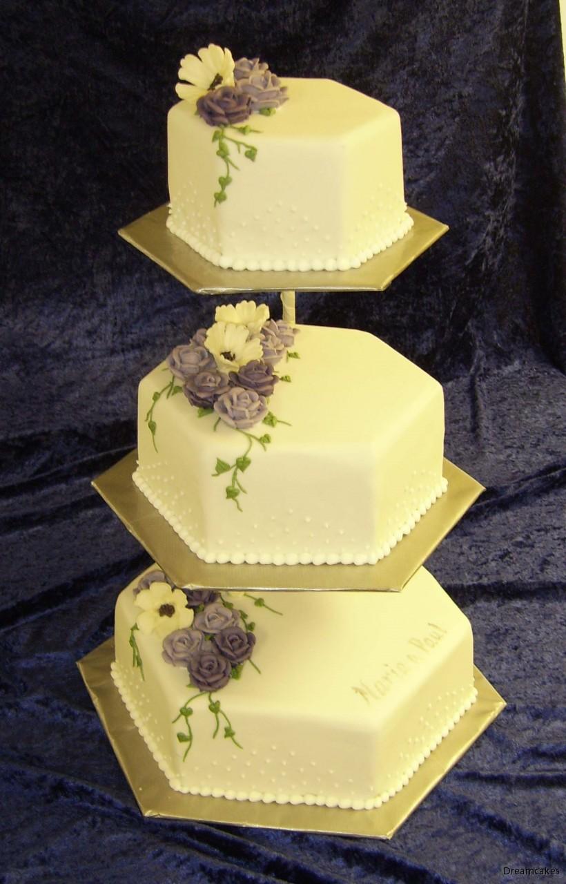 e85614f25d1f Vacker vit bröllopstårta med spritsad pärlbård, spritsade blommor i lila  och vitt.