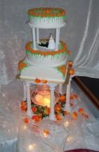 Bröllopstårta med spritsade rosor i orange och fontän under tårtan.