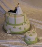 Bröllopstårta i två våningar, färgtema vitt och grönt. Bakelsen bredvid är glutenfri.