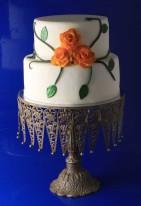 Vit bröllopstårta av marsipan, med orange rosor och gröna rosblad. Rosbladen har täckts med ätbart glitter.