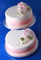 Bröllopstårta i två våningar, vit marsipan med rosa detaljer. Vackra rosbuketter pryder tårtan