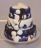 Bröllopstårta med havsmotiv i marinblått och vitt. Tårtan är klädd med marsipan och har detaljer av sockerpasta.