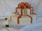 Liten bröllopstårta som paket med klättrande brudpar