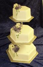 Vacker vit bröllopstårta med spritsad pärlbård, spritsade blommor i lila och vitt.