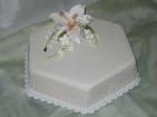 Enkel bröllopstårta med en liljebukett i socker. Spritsade kanter av kristyr.