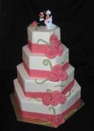 Söt bröllopstårta i 4 våningar. Klädd i vit marsipan och rosa marsipanrosor.