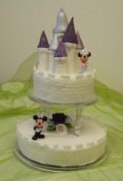Fantasifull bröllopstårta i form av ett sagoslott, med Mimmi och Musse Pigg som brudpar. Slottet är gjort av socker.