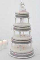 Stilren bröllopstårta i vitt och silver, dekorerad med små rosa fjärilar.