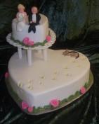 Personlig bröllopstårta till ett litet bröllop. Klädd i vit sockerpasta, spritsade rosor och modellerad familj.