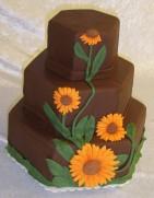 Våningstårta av choklad med stora solrosor. Höstig bröllopstårta i vackra färger.