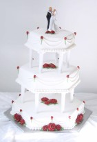 Vacker, elegant och klassisk är denna vita bröllopstårta i 3 våningar, dekorerad med röda spristade rosor.