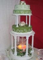 Tre gröna nyanser med vita spritsade löv. Klassisk bröllopstårta i omvänd färgkombination.