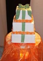 Som en vitt bröllopspresent är denna vita våningstårta med orange modellerade tårtrosor.