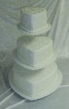 Vit hjärtformad bröllopstårta med spritsat mönster av kristyr.