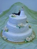 Romantisk bröllopstårta i vit sockerpasta med cremefärgade rosor av socker