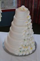 Stor bröllopstårta i många våningar med ett fall av kallor utmed ena sidan. Kallorna är ätbara och gjorda av socker.