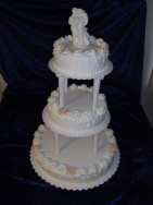 Elegant våningstårta med spritsade rosor. Bröllopstårtan är klädd i sockerpasta.