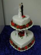 Bröllopstårta i två våningar med spritsade rosor i olika röda nyanser.