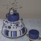 Lila och vit bröllopstårta med liten extra bakelse för glutenallergiker. Modellerat brudpar på toppen.