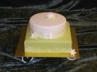 Vit och grön bröllopstårta enkelt dekorerad med mönstrat band och några små liljor av socker. Tårtan är klädd med sockerpasta.