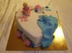Kombinerad dop- och födelsedagstårta klädd i vit sockerpasta dekorerad med baby, barn, filt och blommor av sockerpasta.