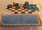 Doptårta med modellerad baby, leksaker och filt modellerad i socker. Schackrutigt golv av sockerpasta.