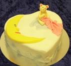 Söt doptårta med dopnalle och månskära. Tårta klädd med sockerpasta.