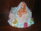 Ljuvlig doptårta där badbabyn täcker nästan hela tårtan. Babyn är gjord av socker, detaljer av sockerpasta och sprisade bubblor av kristyr.
