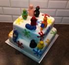 Färgglad doptårta med Barbapappa och Barbafamiljen. Tårta i vit sockerpasta med modellerade figurer i socker.
