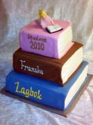"""Studenttårta i tre våningar av """"böcker"""". Modellerad student i socker."""