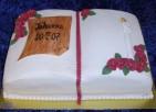 Konfirmationstårta i form av psalmbok/bibel. Täckt med vit sockerpasta, plakett, ljus och blommor av socker.
