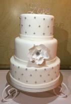 Diamantmönstrad bröllopstårta i vitt med silverpärlor och diamantornament. Vit sockerblomma av flowerpaste.