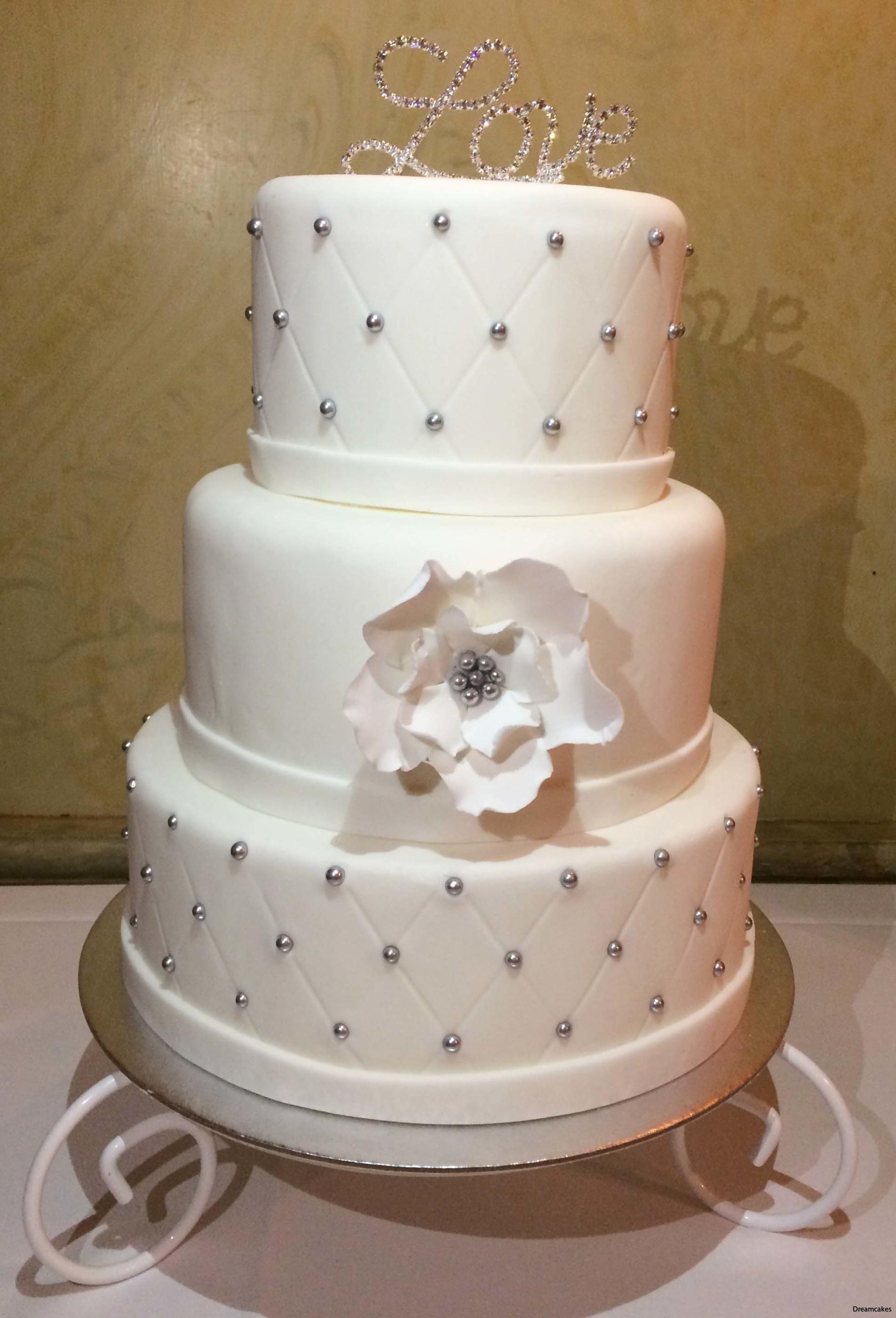 53093095e3be Diamantmönstrad bröllopstårta i vitt med silverpärlor och diamantornament.  Vit sockerblomma av flowerpaste.