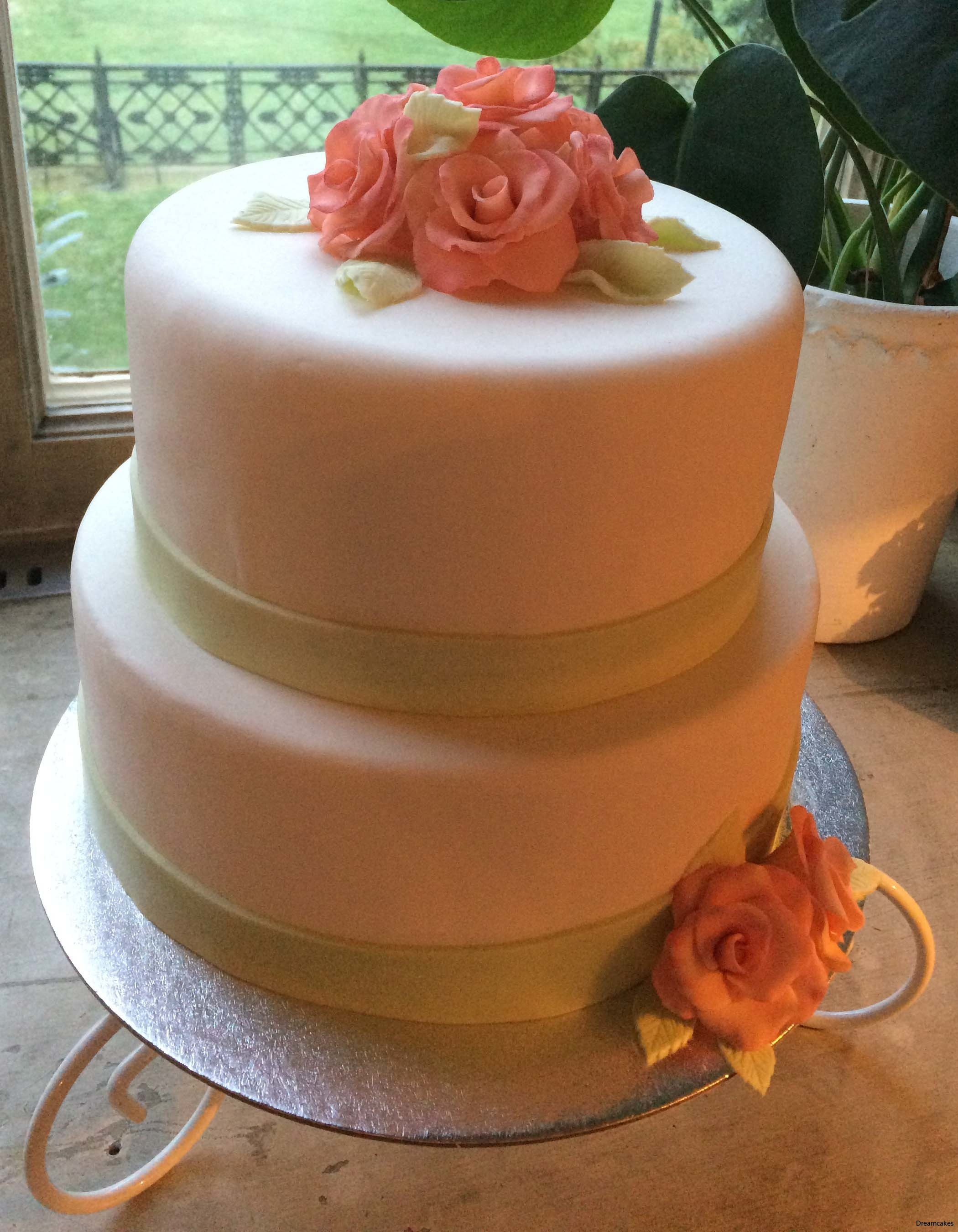 7d6c4479b2c3 Våningstårta till bröllopet med apricosrosa rosor och gröna detaljer.  Tårtan är klädd i sockerpasta.