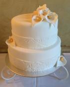 Elegant bröllopstårta helt i vit sugarpaste med mönstrad bård och callaliljor