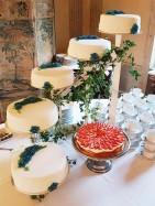 Spritsade blåklint av kristyr dekorerar denna vita bröllopstårta klädd med sockerpasta.