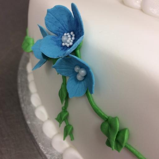 Bröllopstårta i två våningar med söta blå bommor på sidorna