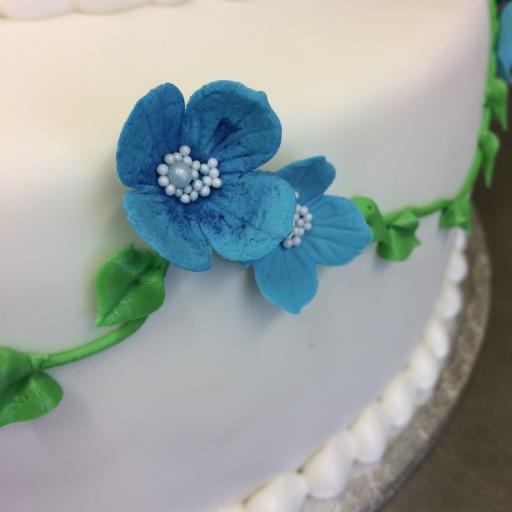 Blå sockerblommor av flowerpaste och spritsade gröna blad på en vit våningstårta