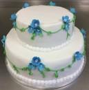 Bröllopstårta i två våningar, klädd med vit sockerpasta, spritsad pärlbård och bladgirlanger av krityr. Blå blommor med pärla i mittpunkt.