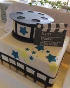 """""""Filmtårta"""" till filmstudenten. Klapp och filmrullens topp är av modelleringspasta, skrift av vit pulverfärg. Övrig dekor är av sockerpasta. Innehåll Blåbärs- och citronmousse."""