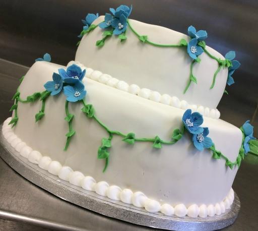 Våningstårta till bröllopet med blå blommor runt hela tårtan