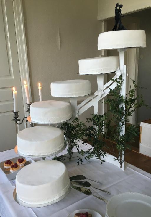 Bröllopstårta helt i vitt klädd med sockerpasta, mönstrad bård och siluettebrudpar på toppen.