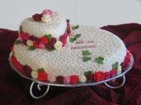 Bröllopstårta i marsipan med spritsade detaljer och rosor.