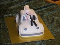 Charmig bröllopstårta i form av en bil. Biltårtan är klädd i vit marsipan. Modellerat brudpar i socker.