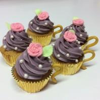 Söta tekoppsmuffins med guldigt handtag och rosa ros i socker.